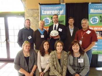 The Lawrence Community team, leadership pictured above, saved the highest total amount of any community. They hold a basketball signed by Kansas Governor Brownback. The basketball signifies both the sport's history in Kansas, as well as the fact that the average Kansas home has enough energy leaks in their home to equal a basketball-sized hole in their roof.
