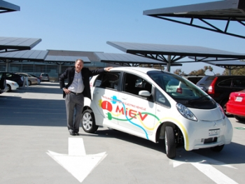 Byron Washom, Director of Strategic Energy Initiatives at the University of California at San Diego, poses with an electric vehicle and some of the solar panels that cover UCSD's campus.| Photo courtesy of UCSD