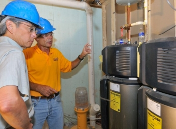 Sec. Chu observes as workers demonstrate energy efficient water heaters. | Department of Energy Photo | Courtesy of National Renewable Energy Laboratory |
