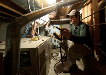 Olaf Sander and Zump Urycki evaluate the heating system of a home in Loveland, Colorado, as part of the Weatherization Assistance Program. | Credit: Dennis Schroeder, NREL.