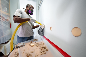 William Stewart, with Veterans Green Jobs, blows cellulose insulation in the interior walls of a Lakewood, Colorado, home. This home is part of the Energy Department's Weatherization Assistance Program that supports energy efficiency upgrades to low-income homes in Denver.   Photo courtesy of Dennis Schroeder, NREL.