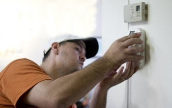 Brian Bernal installs a carbon monoxide detector for a homeowner participating in the Weatherization Assistance Program in Loveland, CO. | Credit: Dennis Schroeder, NREL.