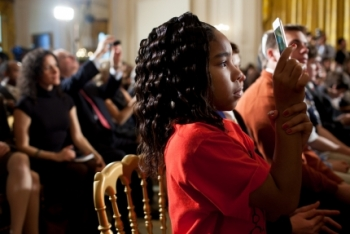 """Ma'kese Kesley takes a picture as President Barack Obama delivers remarks during the second White House Science Fair in the East Room of the White House, Feb. 7, 2012. Join Ma'kese and others for a """"We the Geeks"""" hangout this Thursday. (Official White House Photo by Pete Souza)"""