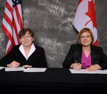 Alice Williams of EM, left, and Joan Miller of the Atomic Energy of Canada Limited, sign a Statement of Intent (SOI).