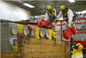 Workers process the first box of waste in the new facility.
