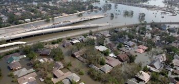This aerial photo of New Orleans from August 29, 2005, shows a flooded neighborhood with a roadway going down into flood waters. Photo courtesy of FEMA/Jocelyn Augustino