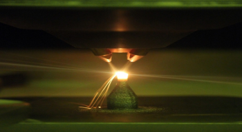 Green light reflection from a low-oxygen environment 3D printer laser deposition of metal powder alloys. Photo courtesy of The Critical Materials Institute, Ames Laboratory
