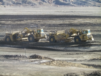 Two scrapers work together to excavate Mancos Shale at the Crescent Junction site to create the second portion of a disposal cell for uranium mill tailings