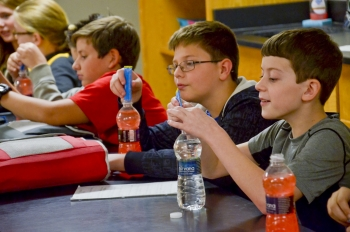 Middle school students work with water bottles and powdered drink mix to learn how contamination interacts with surface and groundwater.