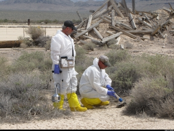 Radiation Control Technicians (RCTs) survey old radium dials remaining at the site of the historic Hamilton atmospheric nuclear test conducted at 8am on October 15, 1958, in Area 5 of the NNSS. This site is undergoing investigation to determine what corrective actions, if any, are necessary. The wood debris seen in the mound behind the RCTS is what remains of the 50-foot tower upon which the nuclear device was detonated (yield of 1.2 tons).