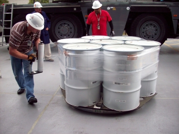 Operators prepare drums of contact-handled transuranic waste for loading into transportation containers