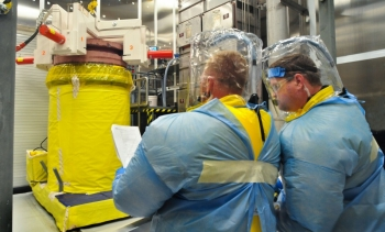 Workers process and repackage waste at the Transuranic Waste Processing Center's Cask Processing Enclosure.