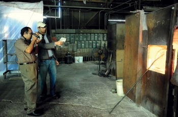 Gopala and a student conduct an energy assessment on a glass-melting furnace.<br /><em>Courtesy of WVU</em>