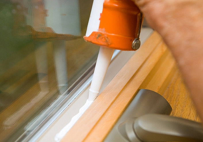 Applying Caulk To A Window Frame To Prevent Air Leakage. This Caulk Is  White When