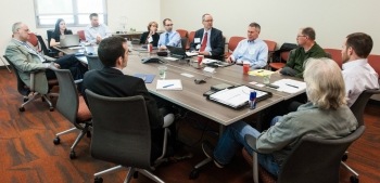 Photo of a roomful of people at a table in a meeting.