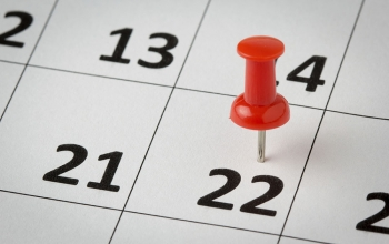 Photo of a red thumbtack marking a date on a calendar.