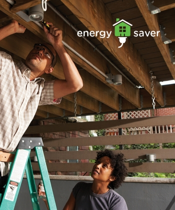 Photo of a man on a ladder doing electrical work, while a woman stands beside him to assist.