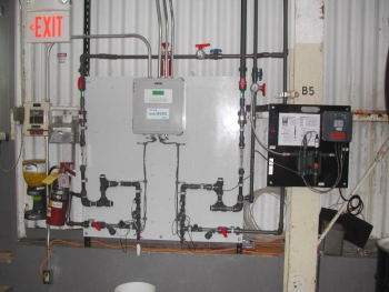 A metal wall has an advanced cooling tower control system mounted on it. There is a white control panel with series of pipes running in and out of it along the metal wall.