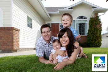Photo of a family -- a mom, a dad, and two kids -- smiling in front of a house.
