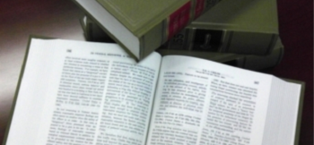 An open lawbook with a closed lawbook touching the top corner of the left open page.