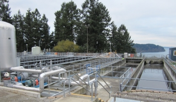 Image shows the tanks, pipes, and water holding areas of a wastewater treatment plan. Trees, shrubs, and a body of water are in the background.