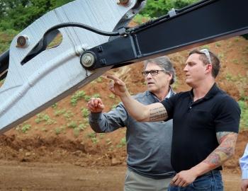 Matt Sallas shows Energy Secretary Rick Perry some of the MDF's work.