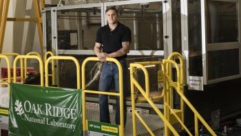 Matt Sallas stands outside of the BAAM machine at Oak Ridge National Laboratory.