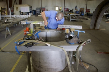 A project engineer with EM contractor North Wind, inspects fabrication of a new hatch cover.