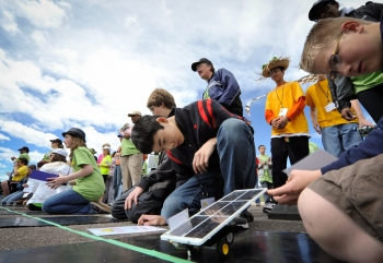 Students line up at the starting line to race solar cars.