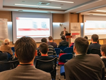 People sitting in chairs in a conference room with a trainer standing to the side of a screen with a Powerpoint presentation displayed.