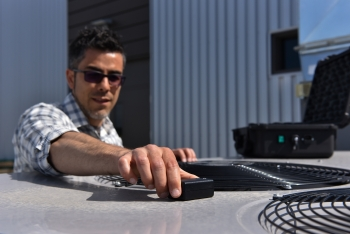 A man places a sensor on an HVAC system outside of an office building.