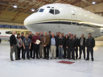 An airplane image with the group of people in front depicting aviation management