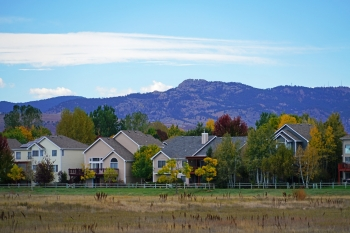 Photo of a row of houses with mountains rising beyond.