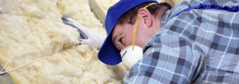 Photo of a man working on insulation in a building, wearing a hat and a face mask.