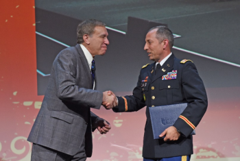 Photo of two men shaking hands at a public event.