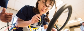 A student holds a screwdriver and she adjusts her project in the Collegiate Wind Competition