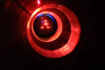 PipeDream measures the volume of surrogate deposits while spiraling sensors through a test pipe. Its headlights alternate white and ultraviolet to acquire the visual and fluorescent appearance of the surrogate deposits.