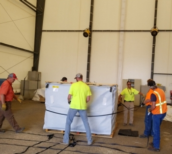 Workers conduct macro encapsulation to treat waste inside the soft-sided building.