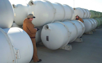 Workers inspect one of the thousands of specially designed storage cylinders that hold DOE's inventory of more than 740,000 metric tons of depleted uranium hexafluoride (DUF6).