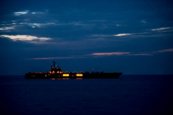 A U.S. Navy nuclear-powered aircraft carrier at night