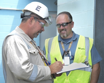 Fluor-BWXT Facility Manager Doug Davis (left) and employee Carl Faub complete paperwork to approve the cylinder for transport.