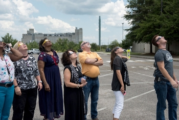 SRS employees look up at the eclipse. In the background is the Defense Waste Processing Facility (DWPF), the nation's only operating vitrification facility that converts high-level radioactive waste into a glass form safe for long-term storage.
