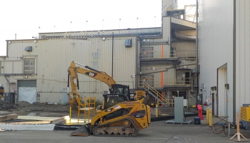 Demolition equipment is staged in front of the Vitrification Facility.