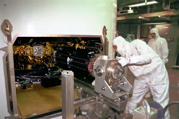 At Launch Complex 40 on Cape Canaveral Air Station, workers are installing three Radioisotope Thermoelectric Generators (RTGs) on the Cassini spacecraft.
