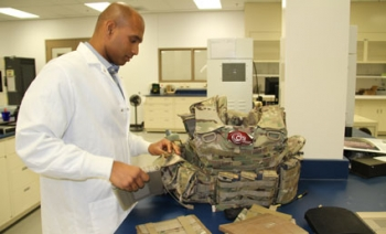A researcher works on a machine as he develops light weight equipment for soldiers.