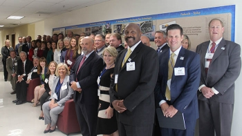 members of the chamber and DOE leaders pose by a wall display in DOE's Forrestal Building highlighting the history, operations, and cleanup at the Paducah Gaseous Diffusion Plant.