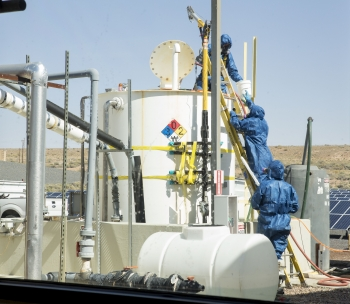 Workers wear personal protective equipment (PPE) while performing acid-neutralization activities.