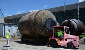 Workers move a 33-ton converter. More than 1,700 similar pieces of the process gas equipment will be cut into segments and allow their steel shells to be safely placed in the Onsite Waste Disposal Facility.