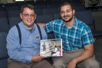 Bill Wabbersen, left, holds a photograph from 2003 when he taught students about engineers at Davidson Fine Arts. Thomas Nail, right, is pictured in the photo immediately below (second from left) as a seventh-grader in Wabbersen's class.