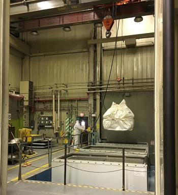 Crews at the 324 Building use a crane to lift a large piece of packaged waste, retrieved from the building's airlock, into a waste box for shipment to the Hanford Site's regulated landfill.